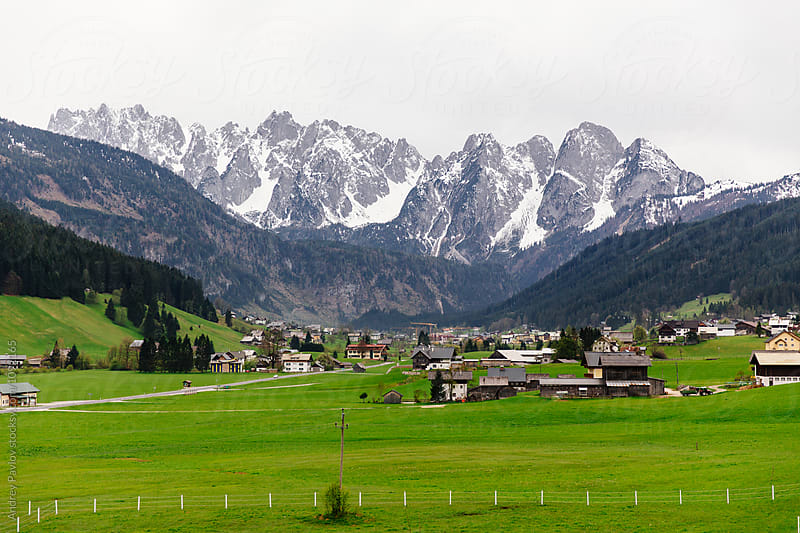 Austrian village against of rocky mountains in snow by Andrey Pavlov for Stocksy United