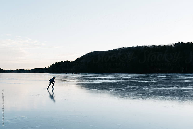 boy skating on a lake in the evening by Léa Jones for Stocksy United