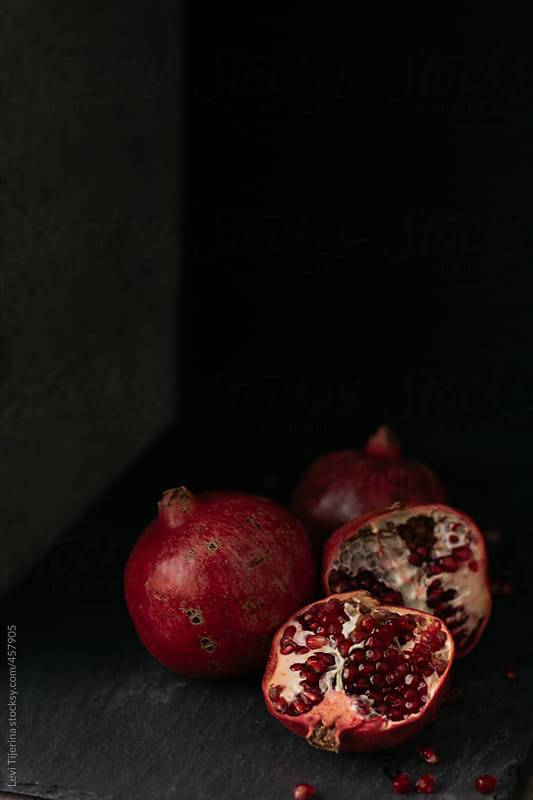 pomegranate seeds on wood table and slate by Levi Tijerina for Stocksy United