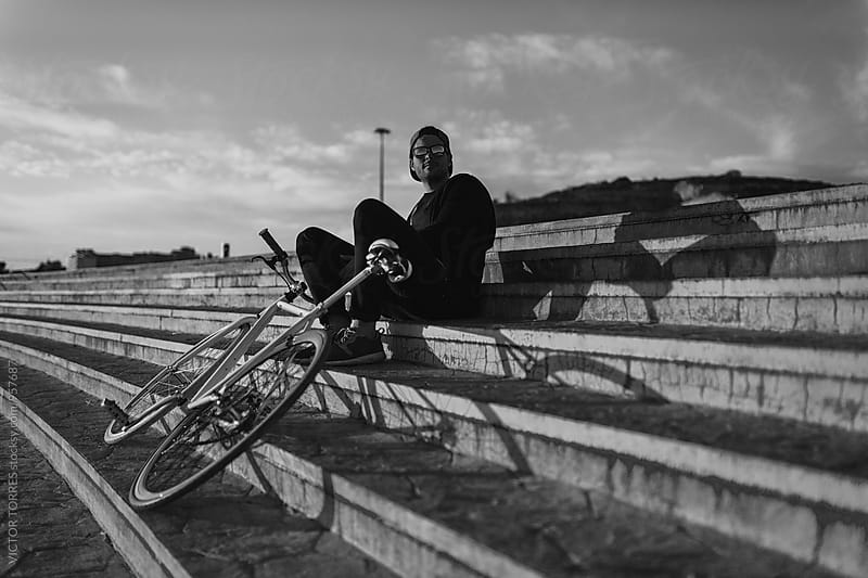 Young Man Resting Besides His Bicycle by Victor Torres for Stocksy United