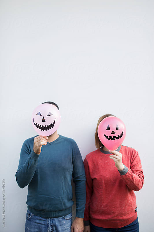 Couple is hiding behind a halloween balloon by Jovana Rikalo for Stocksy United