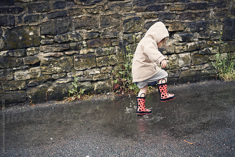 Child playing in the puddles on a rainy day by sally anscombe for Stocksy United