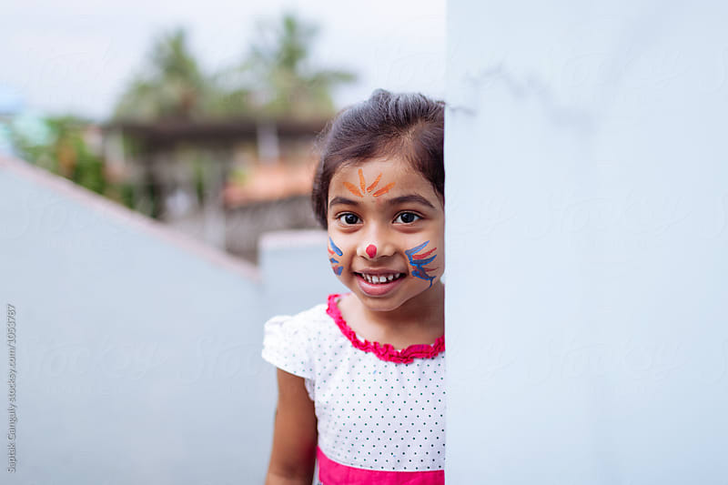 Little girl with face paint peeking from behind a wall by Saptak Ganguly for Stocksy United