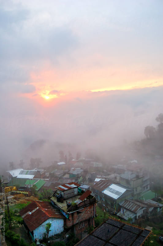 A foggy sunset and houses in Sikkim,India by Saptak Ganguly for Stocksy United
