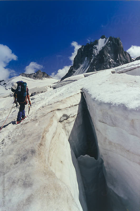 Climber walking on glacier next to open crevasse in the mountains. by Soren Egeberg for Stocksy United