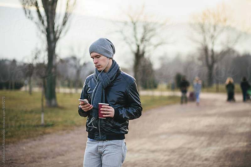 Young man using his smartphone, with headphones plugged in the park by Aleksandar Novoselski for Stocksy United