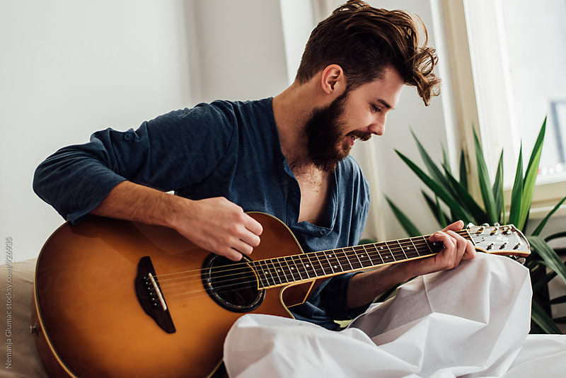 Bearded Man Playing Guitar in Bed by Nemanja Glumac for Stocksy United