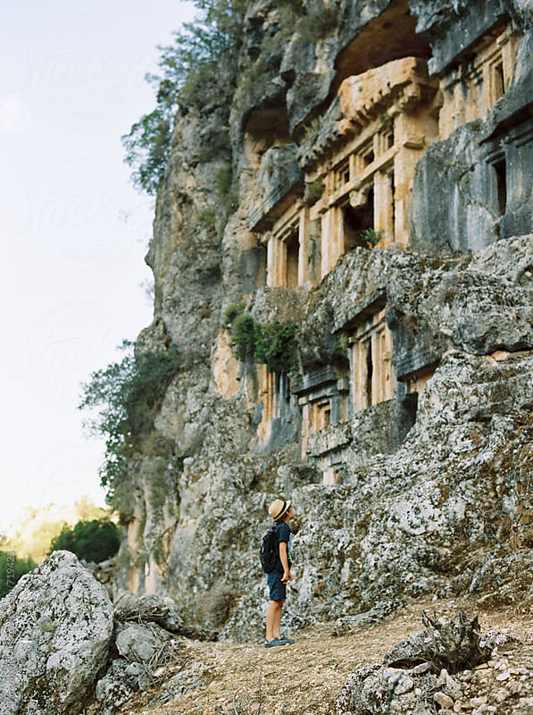 Boy looking up at Lycian tombs in Pinara, Turkey by Kirstin Mckee for Stocksy United