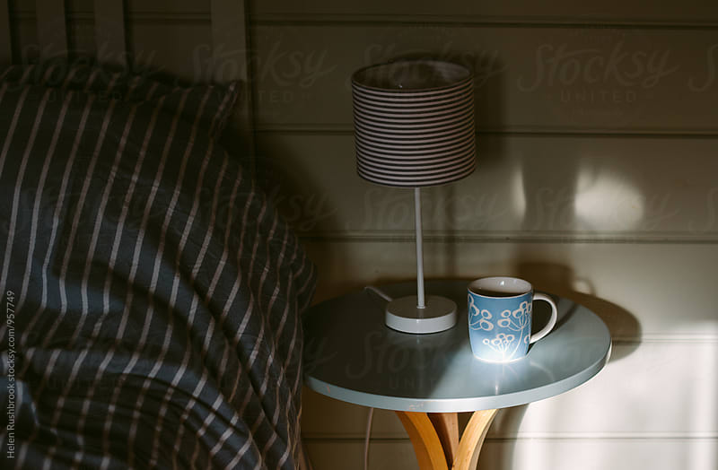 A cup of tea on a bedside table in a blue themed bedroom by Helen Rushbrook for Stocksy United