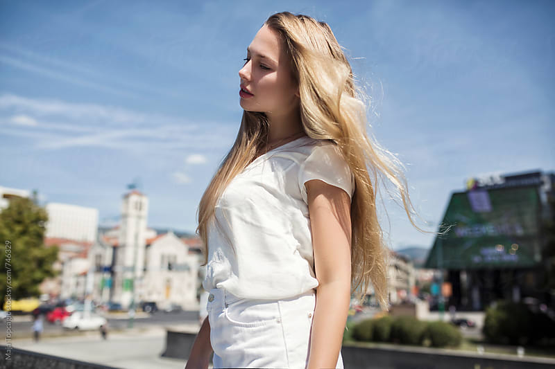 Young beautiful blond woman in the city by Maja Topcagic for Stocksy United