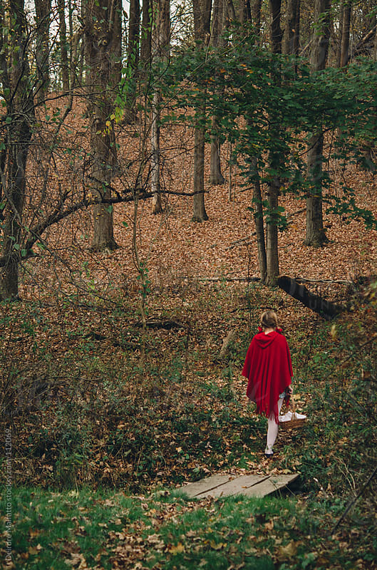 girl in red with basket walking across bridge in woods by Deirdre Malfatto for Stocksy United