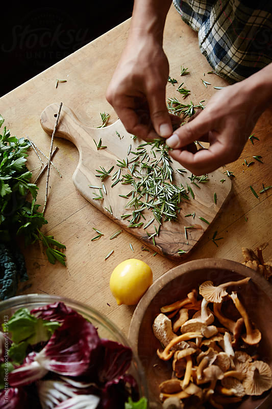 Man preparing herb rosemary for dinner in kitchen by Trinette Reed for Stocksy United