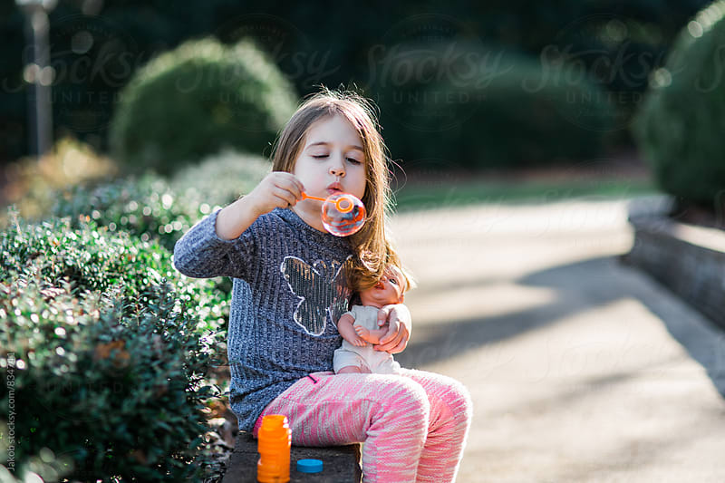 Cute young girl sitting outside blowing bubbles with her baby doll by Jakob for Stocksy United