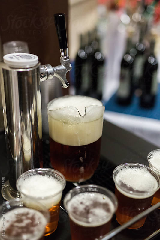 Beer on tap with frothy pints and pitcher by Matthew Spaulding for Stocksy United