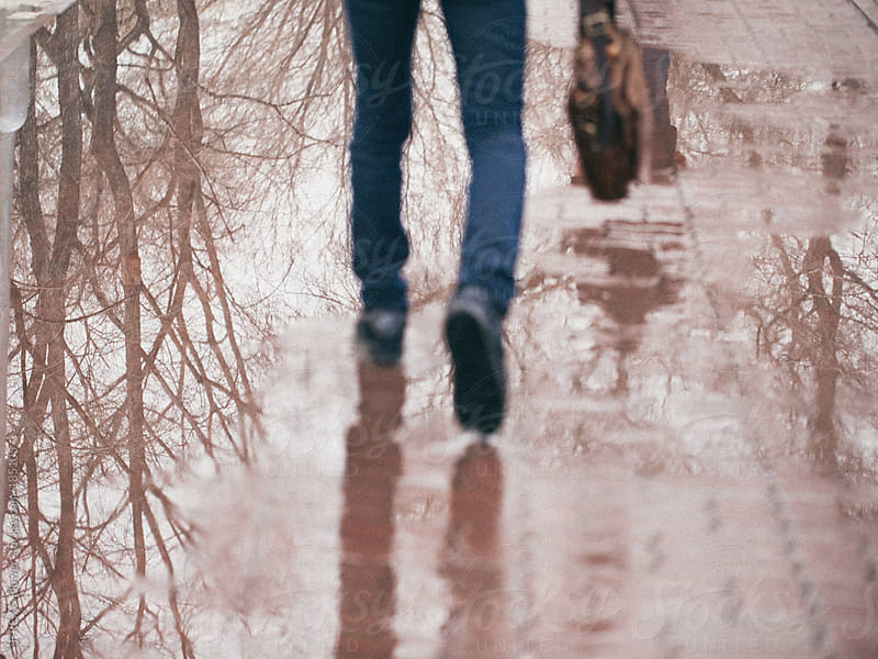 Person walking on a puddle by T-REX & Flower for Stocksy United