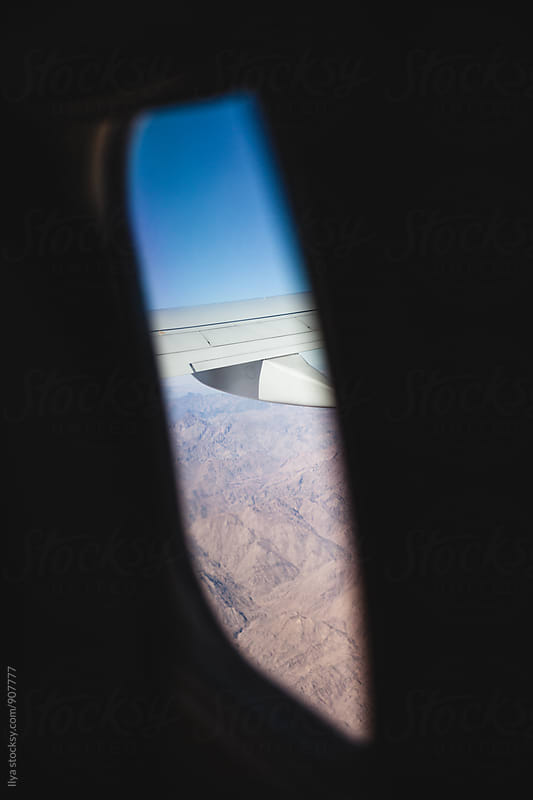 View of the plane wing, Egypt desert shot through airplane window by Ilya for Stocksy United