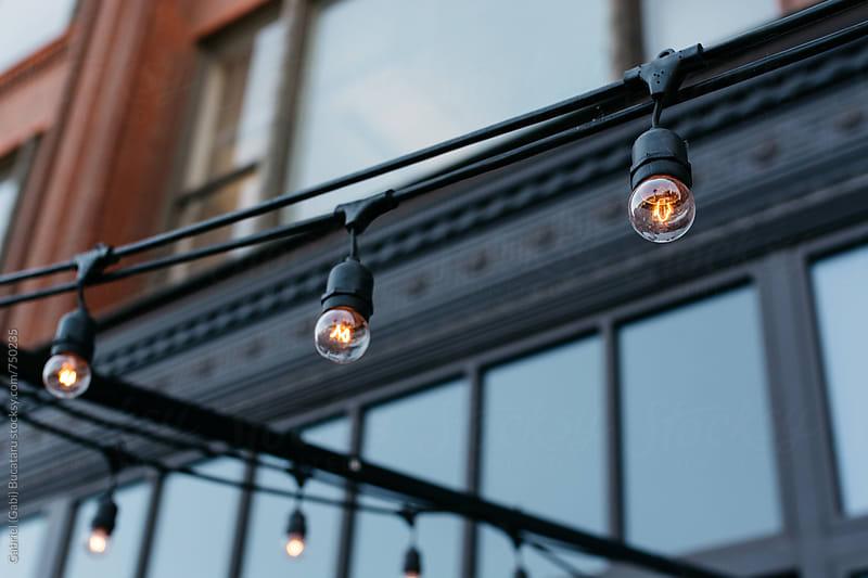 Ornamental light bulbs in front of a building by Gabriel (Gabi) Bucataru for Stocksy United