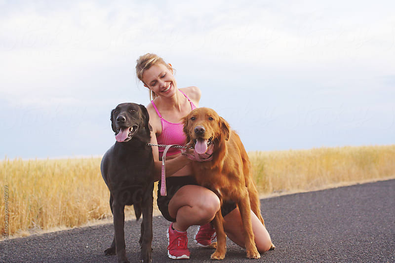 Woman runner stops to pet her dogs. by Tana Teel for Stocksy United