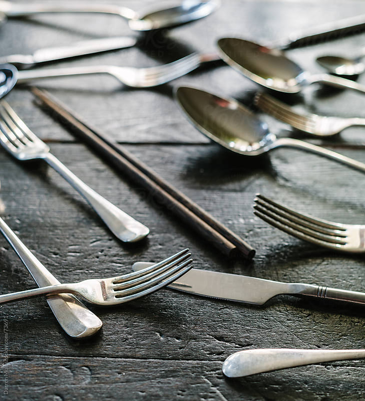 Cutlery strewn across a table.  by Darren Muir for Stocksy United