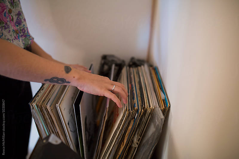 Woman choosing records by Reece McMillan for Stocksy United