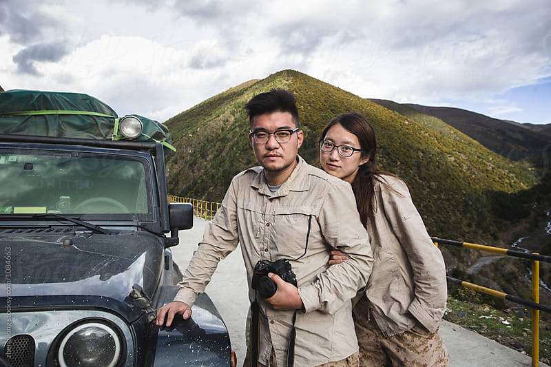young couple stand beside SUV by zheng long for Stocksy United