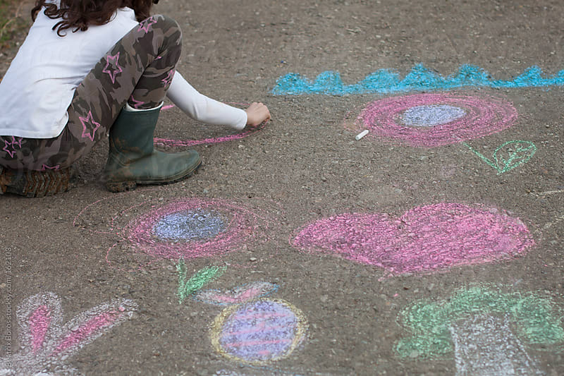 Girl drawing with chalk on a country road  by Beatrix Boros for Stocksy United