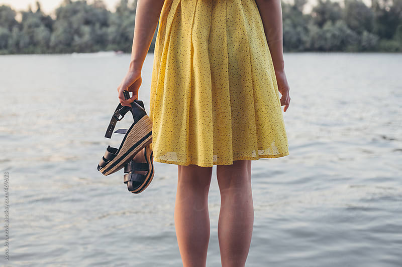 Young woman standing by a lake holding her shoes by Jovo Jovanovic for Stocksy United