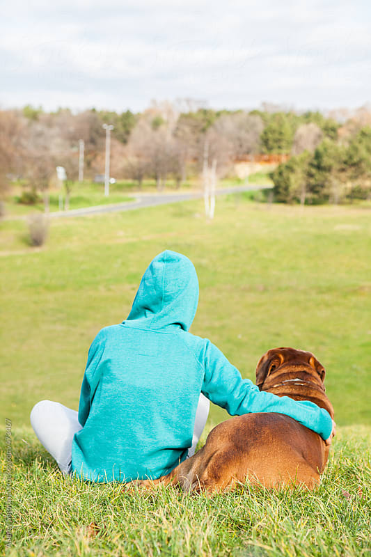 Girl and her dog sitting on top of green meadow and watching nature. by Audrey Shtecinjo for Stocksy United
