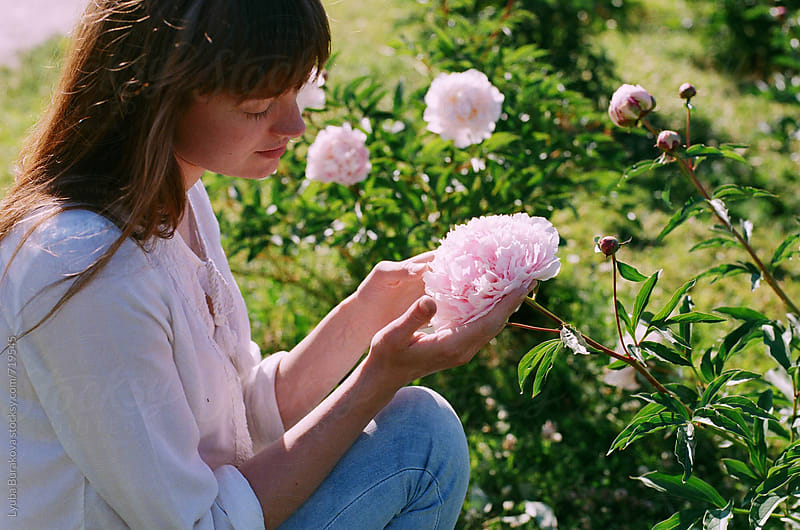 Woman admires peony by Lyuba Burakova for Stocksy United
