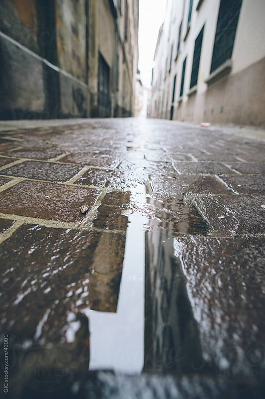 Puddle in empty street during a rainy day by GIC for Stocksy United