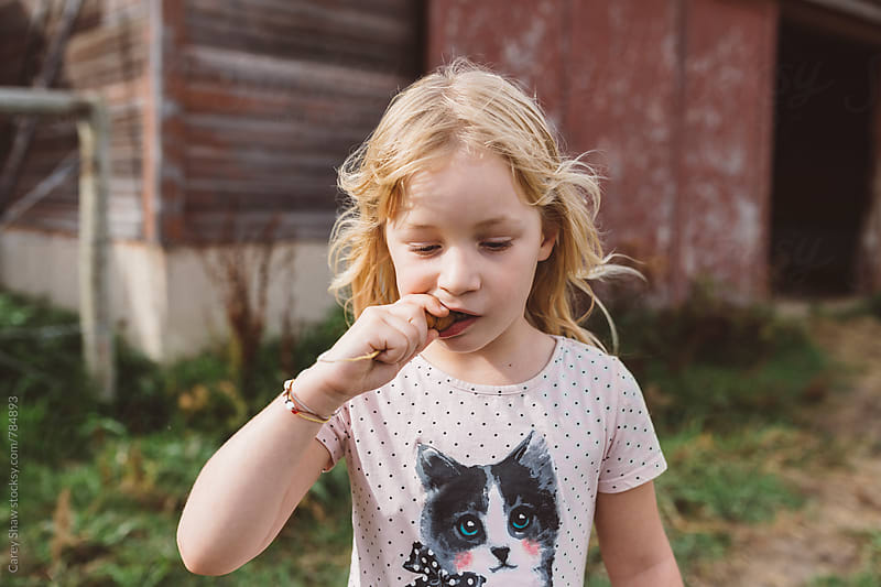Girl taking bite of carrot by Carey Shaw for Stocksy United