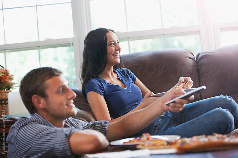 Television: Couple Watching TV and Eating Pizza by Sean Locke for Stocksy United