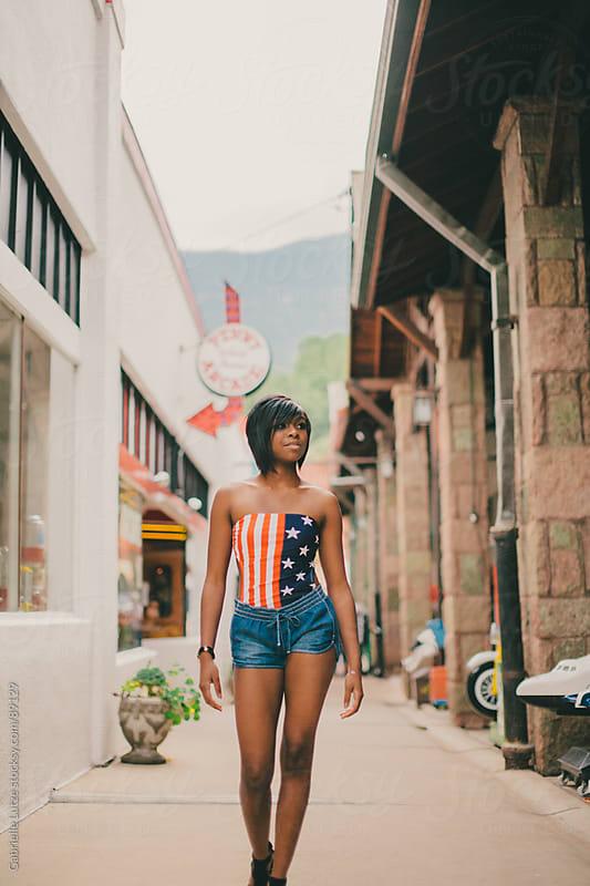 Black girl in Americana top walking by Gabrielle Lutze for Stocksy United