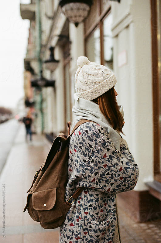 Young woman with a backpack standing on a street by Lyuba Burakova for Stocksy United
