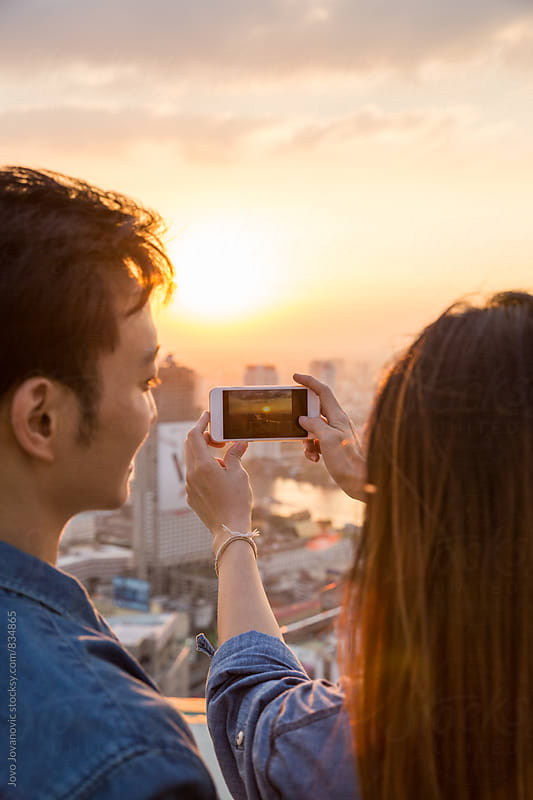 A couple taking a picture of the sunset by Jovo Jovanovic for Stocksy United