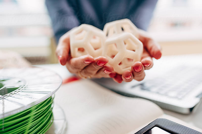 Engineer holding and inspecting 3d printed hexagon design samples by Aila Images for Stocksy United