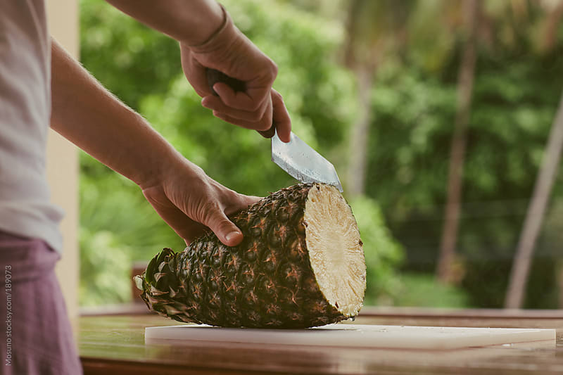 Anonymous Man Cutting Pineapple by Mosuno for Stocksy United