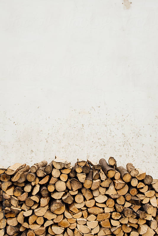 Pile of firewood against the white wall by Boris Jovanovic for Stocksy United