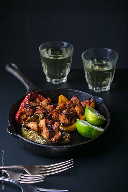 Chipotle chicken: Chipotle chicken stuffed bell peppers in a skillet. by Darren Muir for Stocksy United