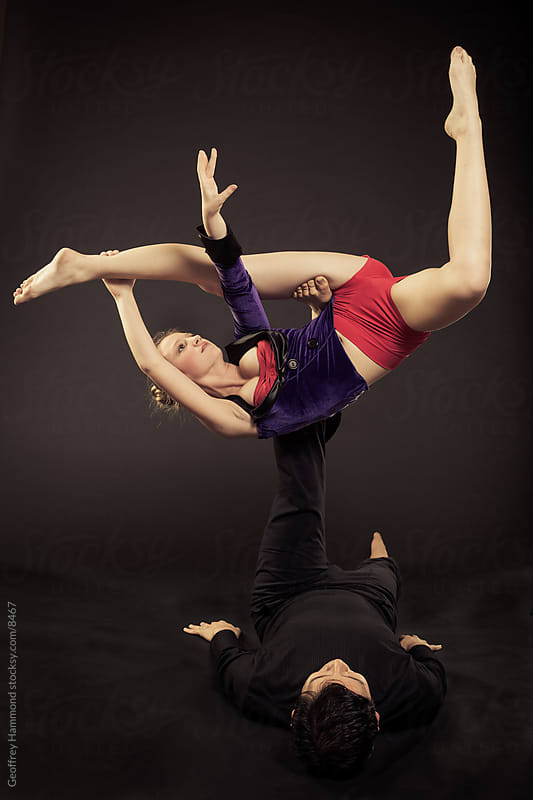 Acroyoga Pair Performing a Hangle Dangle by Geoffrey Hammond for Stocksy United