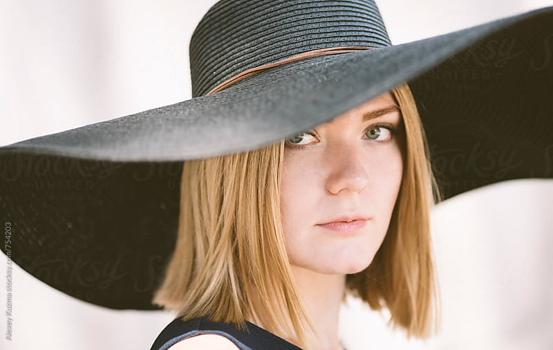 young blond woman with black hat  by Vesna for Stocksy United