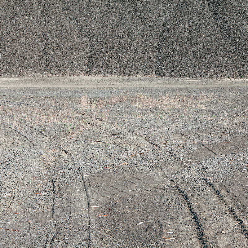 Gravel pile used for road maintenance, tire tracks in foreground, Oregon by Paul Edmondson for Stocksy United