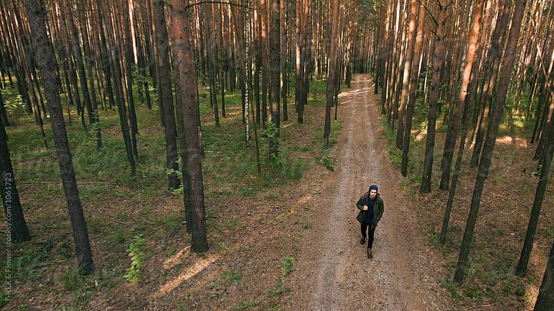 Backpacker in hat walking along forest road by Danil Nevsky for Stocksy United