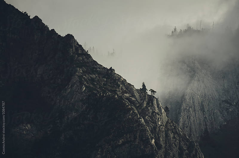 Mountain shrouded in fog by Cosma Andrei for Stocksy United