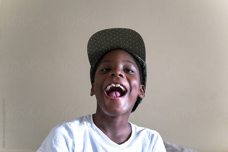 Young boy showing his teeth on his bed by Eddie Pearson for Stocksy United