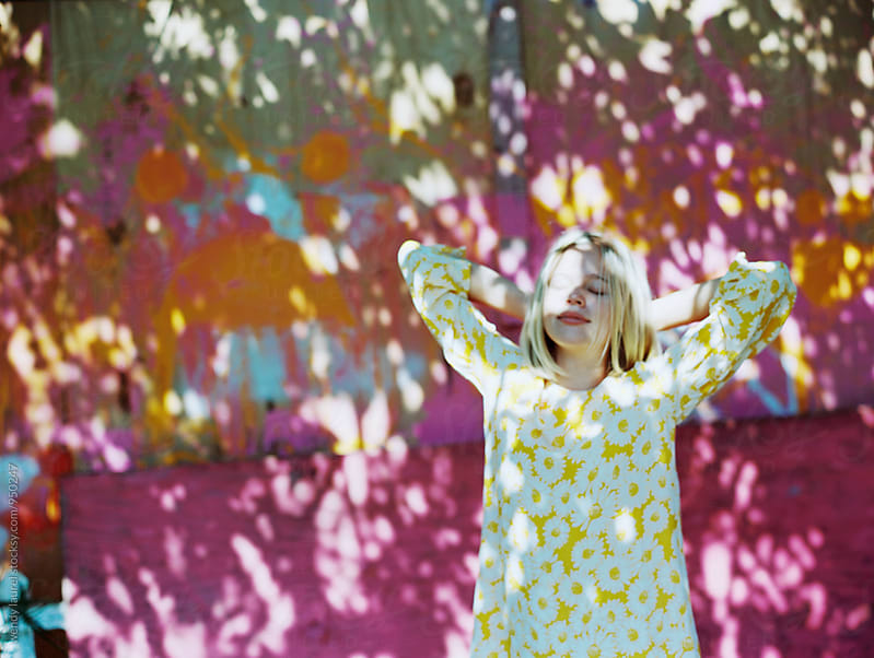 girl in dapplied light with pink and orange mural by wendy laurel for Stocksy United