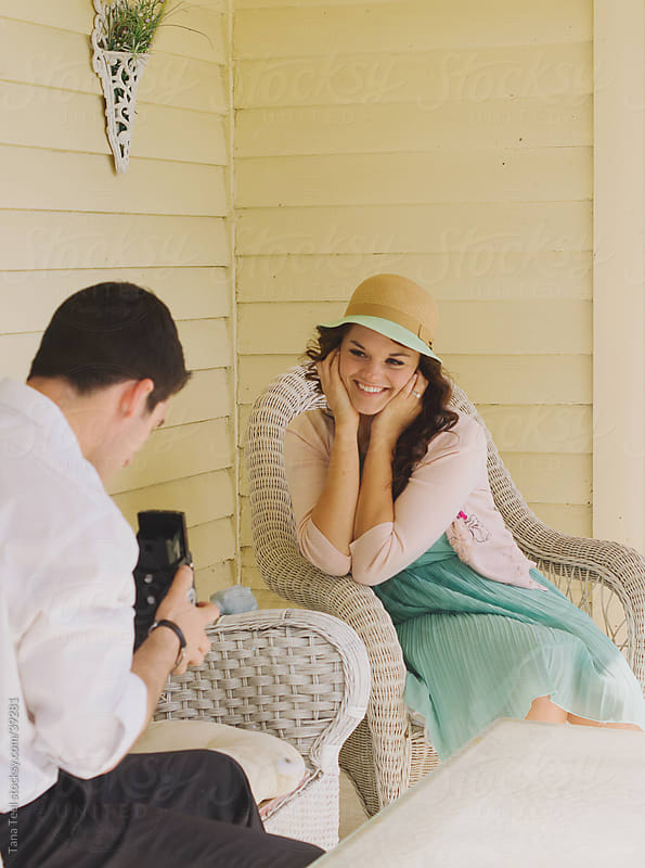 A young man looks through a vintage camera at a young woman.  by Tana Teel for Stocksy United