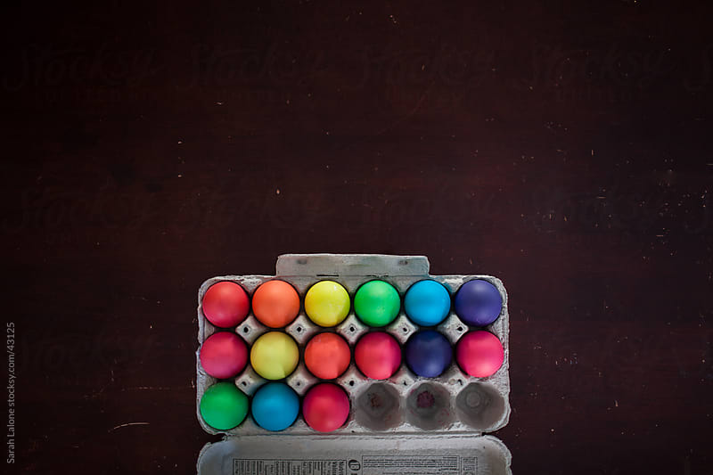 Vividly colored easter eggs in a carton. by Sarah Lalone for Stocksy United