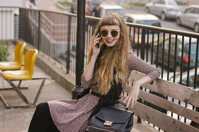 Young woman speaking on the phone by Evil Pixels Photography for Stocksy United