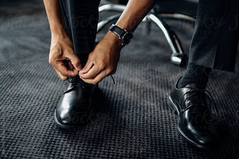 African American man tying black shoes by ZOA PHOTO for Stocksy United